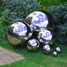 """Use some <a href=""""http://www.thegardenglove.com/how-to-make-mirrored-gazing-balls-for-the-garden/"""" target=""""_blank"""">chrome metallic spray paint</a> to make bowling balls into reflective garden orbs."""