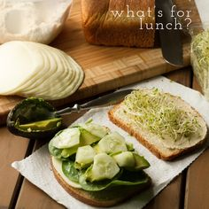 This is hummus, provolone, baby spinach, sliced avocado, cucumbers, and sprouts on my favorite pain de mid sandwich bread.