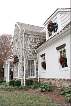 wreath flanked windows of beautiful stone exterior home
