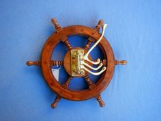 "12"" Nautical Decor Ship Wheel Brass Hooks. Classic teak wood ship's wheel and 4 solid brass hooks.  Make any nautical theme space more functional with this solid brass quad pivoting hook system mounted on a nautical decoration ship wheel.  Light satin finish preserves and accents this teak hardwood.  Solid brass hooks articulate and give several options for hanging coats, clothing, hats and all."
