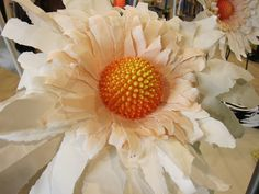 Anthropologie Display, giant daisy made of styrofoam balls, beads, and watercolor paper.