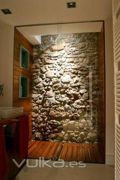Regadera con piso de madera y pared de piedra. Shower wood floor and stone wall.