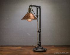 """This industrial table lamp uses a 60 Watt Edison Bulb which hangs from a vintage style cloth cord and offers subtle but brilliant ambient light. The 8"""" copper s"""