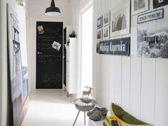 Na ścianie piękne białe deski, podłoga też biała, z żywicy epoksydowej, a dla kontrastu czarne drzwi, w roli tablicy (pomalowane farbą tablicową). Ten przedpokój jest również mini-galerią, zgromadzono w nim wiele osobliwych przedmiotów.