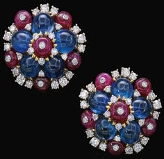 Pair of ruby, sapphire, and diamond earrings. Bulgari, circa 1960's. Each of cluster design, set with cabochon sapphires, polished rubies and highlighted with brilliant-cut diamonds, clip fittings, signed Bulgari, case by Bulgari. Via Sotheby's.