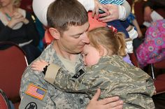 Staff Sgt. Bradley Limbo, of the South Dakota National Guard, holds his two-year old daughter during a welcome home ceremony.