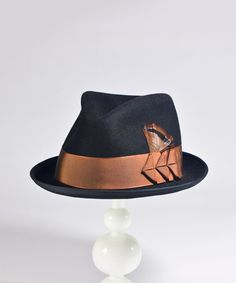 Dandy 'Blake' The 'Blake' is House of Nines Design's take on a classic fedora. The deep tear-drop shaped dent and hand-shaped pinch at the front makes for a substantial, organic look. Trimmed with fancy turkey feathers and hand-folded ribbon arrow motifs. Shown here in classic black, with copper brown antique hatter's ribbon. This hat is made from dense and soft high-quality rabbit fur felt, blocked by hand into shape. Fitted with a top-quality full grain Roan leather sweatband inside.