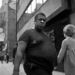 Large-bellied man walking along a city street, looking begrudgingly at the camera. Street Photography 5 | Vivian Maier Photographer