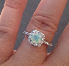 Flashing with Opalescent Rainbows, an ethereal 8mm? cushion cut Ethiopian Opal is surrounded by a halo of Brilliant cut white VS Diamonds in this heavenly ring. Solid 14K White Gold. Handcrafted with #halorings