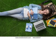 Young female student relaxing outdoors on the grass with laptop and books, she is lying down and smiling at camera - Shutterstock Premier