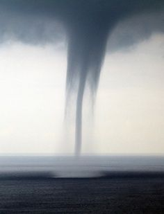 Twin water spouts touch down at sea.