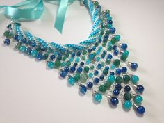 Bib style necklace featuring glass and genuine agate beads hanging from a Kumihimo collar.