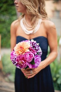 Navy blue bridesmaid dress and layered pearl necklace.--I'd hope to go for a more pink bouquet but the purple goes well and I like the pearls
