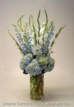 Shabby chic centerpiece of blue hydrangea, delphinium and white gladiolus