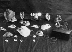 """A selection of some of the items used to disguise facial injury, during the early development of plastic surgery. Included are eyes, ears, noses, and parts of the face, as well as several pairs of spectacles, which were used to disguise the joins and keep some of the parts in place. The original caption reads: """"Repairing war's ravages: renovating facial injuries"""". This photograph was probably taken at 3rd London General Hospital, Wandsworth."""