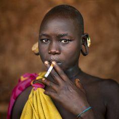 Suri teenage smoking a cigarette,Kibish,Ethiopia