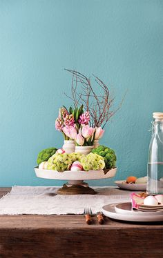 Easter centrepiece flowers floral arrangement Easter eggs mason jars. Place vases filled with spring flowers (like tulips and hyacinths) in the centre of a low cake stand, add brightly decorated eggs, then nestle in chrysanthemums pinned to Styrofoam balls.