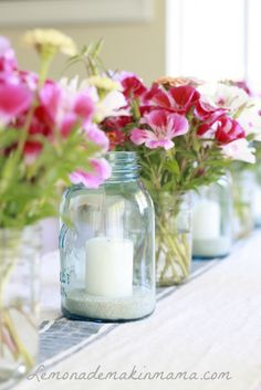 love this.. alternating flowers and candles in mason jars!