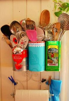 Repurposing cans to hold kitchen items by affixing them to the wall