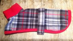 A housecoat style fleece jumper, it slips on easily over the head and then belts around the middle. Made of a grey and red check Tartan fleece, with red neck and trim.  Perfect as a lightweight but really warm coat on dry walks or in the house, or as an under layer on freezing cold wet days. Also brilliant if you go camping or caravanning with your dog, as its an extra layer to keep them warm on cold evenings, and much more practical than covering them with a blanket!  Length refers to the…