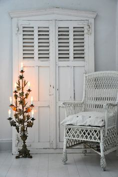 Like the contrast of metal candelabra and white cottage furniture.