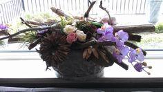Een prachtig groot bloemstuk met hout en kunstbloemen, voor een raam waar geen plant mooi blijft. ( het werden 2 mooie stukken zelfs).