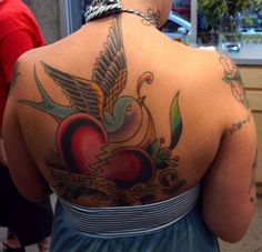 Tattoo on the back of the girl - a broken heart and swallow