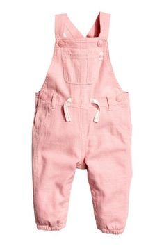 Dungarees in woven fabric with adjustable straps with press-studs, a chest pocket, fake front pockets, real back pockets and a seam at the waist. Press-stud