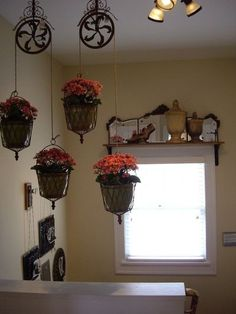 LOVE the idea of old pulleys as plant hangers !