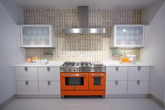 Kitchen vignette featuring a Bertazzoni stove in orange and Swank in the Amaretto Blend ,which is part of Oceanside Glasstile's collection Devotion, in the backsplash. PIRCH Dallas showroom