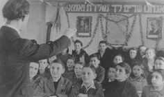 Lyrics to the Jewish national anthem and portraits of Zionist leaders hang in a classroom. Feldafing displaced persons camp, Germany, after April 1945.