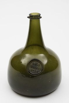 An early 18th century sealed mallet shaped wine bottle: of medium green colour and small size, with raised tapering neck and string rim, with pronounced 'kick up', the shoulders with a seal for 'E. Herbert, 1721, 19 cm high, two small chips to rim.