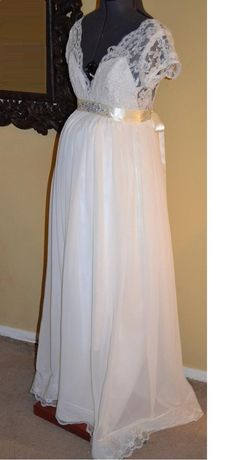 This breath taking ethereal piece is perfect for the pregnant bride. It has a beautiful French lace bodice and a gorgeous rhinestone encrusted sash. Its light and airy chiffon skirt with lace trim hem and a pair of jeweled centered satin bows, accentuates the low cut sexy back. It is maternity bridal at its finest! $550