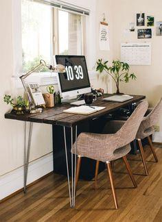 Espacio de trabajo de look totalmente natural con elementos como la madera, en la cubierta del escritorio, y macetas con plantas, que se pueden ver sobre el escritorio y a un costado. Todo frente a la ventana, que da la luz natural perfecta para trabajar.