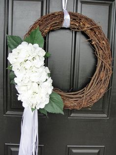 something like this for the church doors... Hydrangea embellished grapevine wreaths