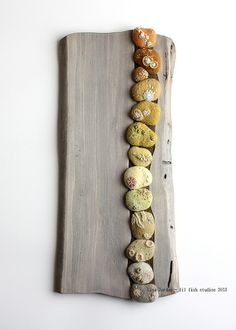 A wall piece I've just completed.  Each wool pebble is made from fiber I've dyed using materials gathered from the woods (and sometimes my kitchen).  They're set into a piece of poplar from my backyard that I planed and aged to a soft grey.