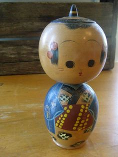 Vintage wooden kokeshi doll with blue kimono, pointy hat, nodding head and signature on bottom by the artist: Minoru Onodira