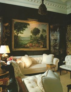 Mark Hampton. A dark living room with beautiful paintings and moulding. Blue was added to the brown paint, a trick used by designer Billy Baldwin when he wanted to avoid too much of a chocolate color. The furniture was all re-upholstered in a cream cotton from Brunshwig & Fils. Photo by Peter Vitale.