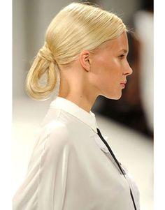 Who says a ponytail has to hang straight? Hairstylist Orlando Pita introduced a bold geometric shape at Carolina Herrera by blowdring the hair with a center part and pulling it into a low ponytail just before looping it underneath the elastic into a triangular form.