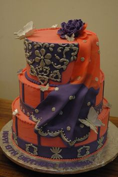 cake resembling 13 th birthday girl's costume, everything edible orange-pink and purple with silver decorations