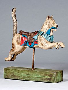 Wood Carved Carousel Cat: Mid-20th century, in the style of Gustav Dentzel, a carved & cream painted running cat with blue ribbon drape, brown saddle over a red blanket, with spiral twist tail. On block-mounted brass pole.