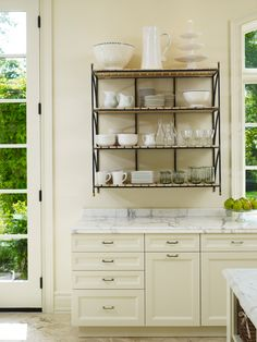 Open Storage: So as not to obscure the light or views, an open iron plate rack provides everyday storage for plates and dishes.