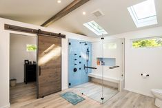 Modern bathroom, lovely detailed with light blue glass tiles, wood beams and barn door
