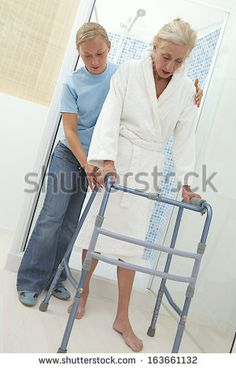 Elderly help keeping an elderly woman secure as she ambulates from  with his walker. On a white background.  - stock photo