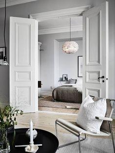 White doors that divide the space between the bedroom and livingroom / Scandinavian style