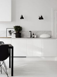 Full white kitchen and grey marble countertop with dots of black with lamps, table, chairs and faucet for chic and concrete effect.