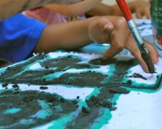 Painting with mud, to make a bogolanfini (Malian mud cloth). Multicultural craft.