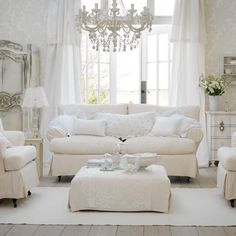White sofa and chairs in front of large French doors