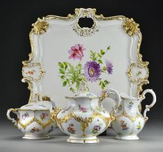 "To include a tray, teapot, covered sugar and a creamer, decorated with floral sprays bordered by raised gilt swags, undersides with blue underglaze and impressed marks, tray measures 16""sq, circa late 19th-early 20th century."