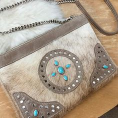 New for Spring: Meet Sinta. This 2-in-1 crossbody/wristlet features our brindle hair-on and Newport leathers. Beautifully hand set with cabochon and turquoise rivet details.  #bohobag #boholeather #bohochic #festivalfashion #coachellafashion #coachellastyle #handbag #clutch